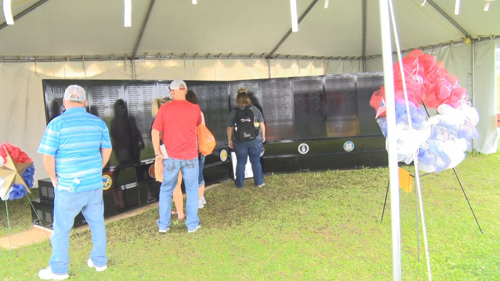 Fair attendees read the names of the servicemen missing in action or killed in combat on the West Virginia Vietnam Veterans Mobile Wall at the State Fair of West Virginia.