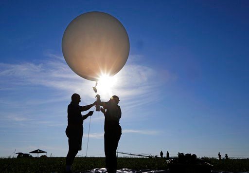 (AP Photo/Mark Humphrey). Mike Newchurch, left, professor of atmospheric chemistry at the University of Alabama in Huntsville, and graduate student Paula Tucker prepare a weather balloon before releasing it to perform research during the solar eclipse.