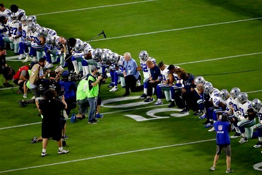 (AP Photo/Matt York). The Dallas Cowboys, led by owner Jerry Jones, center, take a knee prior to the national anthem prior to an NFL football game against the Arizona Cardinals, Monday, Sept. 25, 2017, in Glendale, Ariz.