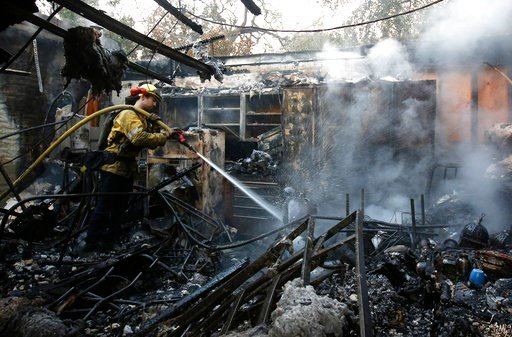 (AP Photo/Rich Pedroncelli). Firefighter Nick Gonzalez-Pomo, of the San Rafael Fire Department, waters down smoldering ashes on a garage Tuesday, Oct. 10, 2017, in Napa, Calif.